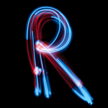 Letter R of the alphabet made from neon sign. The blue light image, long exposure with colored fairy lights, against a black background