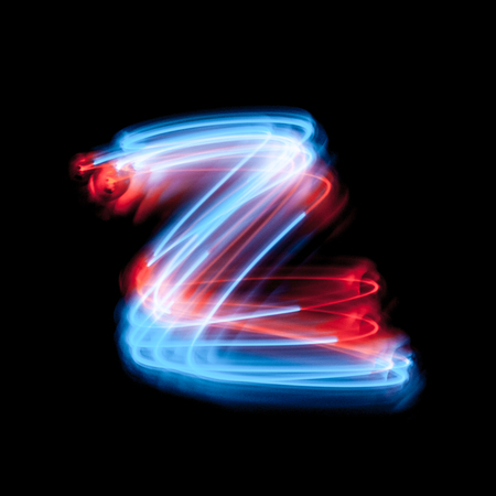 Letter Z of the alphabet made from neon sign. The blue light image, long exposure with colored fairy lights, against a black background Imagens