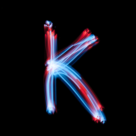 Letter K of the alphabet made from neon sign. The blue light image, long exposure with colored fairy lights, against a black background