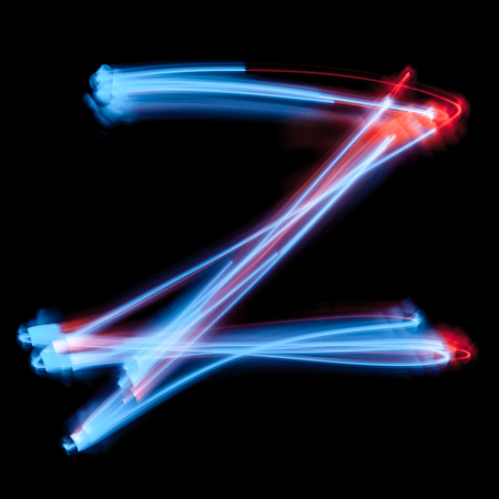 Letter Z of the alphabet made from neon sign. The blue light image, long exposure with colored fairy lights, against a black background 스톡 콘텐츠