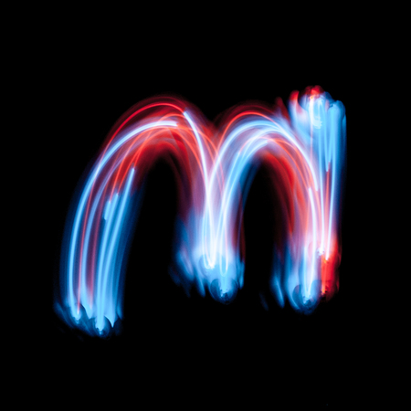 Letter M of the alphabet made from neon sign. The blue light image, long exposure with colored fairy lights, against a black background