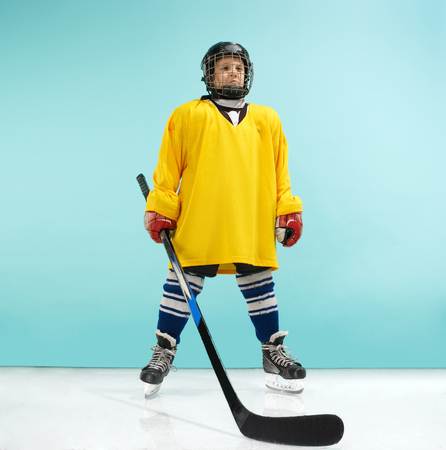 A hockey player in uniform with equipment over a blue studio background. The athlete, child, sport, action concept