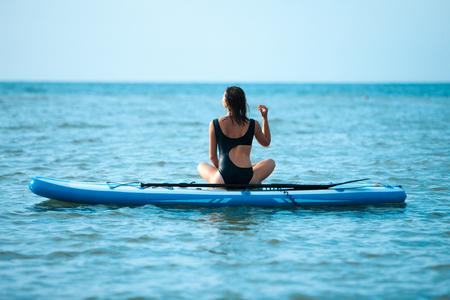 Happy beautiful young girl with paddle board on a tropical beach. Blue sea in the background. Summer, vacation, sup paddleboarding or surfing, travel, lifestyle concept. Reklamní fotografie