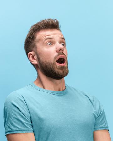 Il giovane sorpreso e stupito che urla con la bocca aperta isolato su sfondo blu. concetto di emozione faccia shock