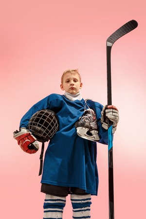 A hockey player in uniform with equipment over pink studio background. The athlete, child, sport, action concept