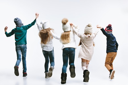 The back view of group of kids in bright winter clothes, isolated on white studio. Fashion, childhood, happy emotions concept Stock Photo