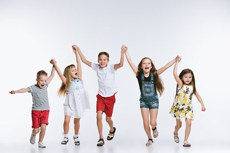 Group of fashion cute preschooler kids friends running together and looking at camera on a white studio background. The friendship, fashion, summer concept. Space for text. Foto de archivo