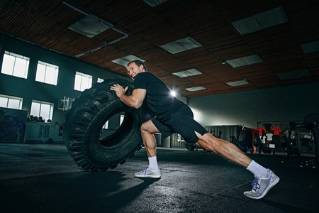 Shirtless young fit man flipping heavy tire at gym. The exercise, fitness, sport, workout, athlete, power, training, bodybuilding concept
