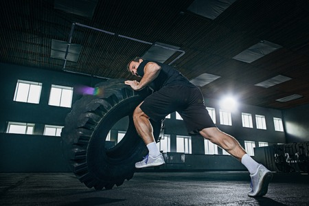 Shirtless young fit man flipping heavy tire at gym. The exercise, fitness, sport, workout, athlete, power, training, bodybuilding concept Stock Photo - 112449869