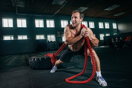 Shirtless young fit man flipping heavy tire with battle rope at gym. The exercise, fitness, sport, workout, athlete, power, training, bodybuilding concept Stock Photo