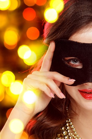 Beauty model woman wearing venetian masquerade carnival mask at party over holiday dark background with magic glow. Christmas and New Year celebration. Glamour lady with perfect make up and hairstyle Reklamní fotografie