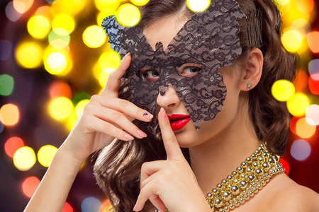Beauty model woman wearing venetian masquerade carnival mask at party over holiday dark background with magic glow. Christmas and New Year celebration. Glamour lady with perfect make up and hairstyle Stock Photo
