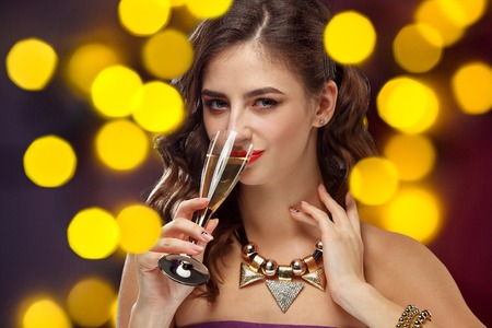 Beautiful girl holding a glass of champagne. Festive mood, shiny background with lights . Celebration of New Year and Christmas, white wine and excitement