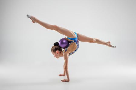 La niña adolescente femenina haciendo ejercicios de gimnasia aislado sobre un fondo gris de estudio. El concepto de gimnasia, estiramiento, fitness, estilo de vida, entrenamiento, deporte