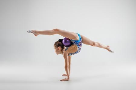 Het tiener vrouwelijke meisje dat gymnastiekoefeningen doet die op een grijze studioachtergrond worden geïsoleerd. Het gymnastiek-, stretch-, fitness-, lifestyle-, training-, sportconcept