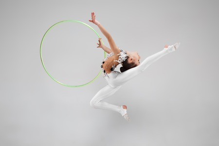 The teen female little girl doing gymnastics exercises with hoop isolated on a gray studio background. The gymnastic, stretch, fitness, lifestyle, training, sport concept