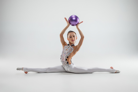 The teen female little girl doing gymnastics exercises with ball on a gray studio background. The gymnastic, stretch, fitness, lifestyle, training, sport concept Imagens - 112674490