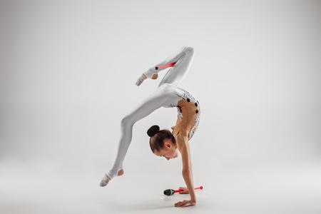 La bambina femmina adolescente facendo esercizi di ginnastica con mazze isolate su uno sfondo grigio studio. La ginnastica, l'allungamento, il fitness, lo stile di vita, l'allenamento, il concetto di sport