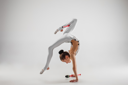 The teen female little girl doing gymnastics exercises with clubs isolated on a gray studio background. The gymnastic, stretch, fitness, lifestyle, training, sport concept 免版税图像