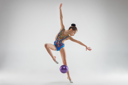 The teen female little girl doing gymnastics exercises with ball on a gray studio background. The gymnastic, stretch, fitness, lifestyle, training, sport concept 스톡 콘텐츠 - 112674575