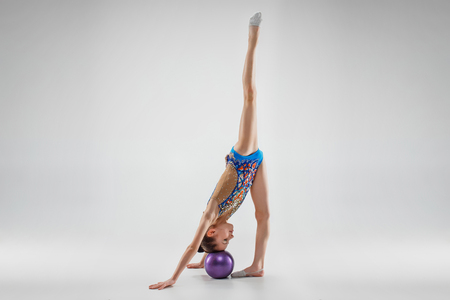 The teen female little girl doing gymnastics exercises with ball on a gray studio background. The gymnastic, stretch, fitness, lifestyle, training, sport concept