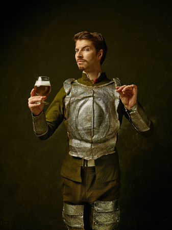 Medieval knight with beer on dark studio background. Portrait in low key of brutal man in tradishional retro costume of spanish hidalgo. Human emotions, comparison of eras and facial expressions concept