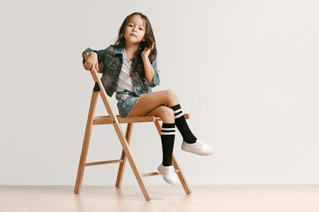 Full length portrait of cute little kid girl in stylish jeans clothes looking at camera and smiling against white studio wall. Kids fashion concept 免版税图像