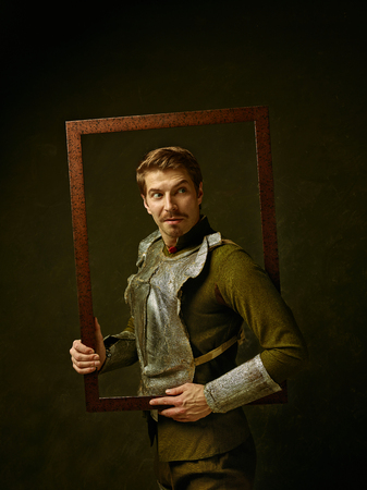 Medieval knight on dark studio background. Portrait in low key of brutal man in tradishional retro costume of spanish hidalgo. Human emotions, comparison of eras and facial expressions concept