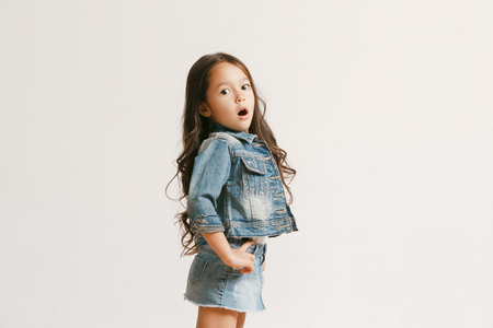 The portrait of cute little kid girl in stylish jeans clothes looking at camera and smiling, standing against white studio wall. Kids fashion concept Banque d'images