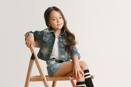 Het portret van een schattig klein meisje in stijlvolle jeanskleding die naar de camera kijkt en glimlacht, zittend tegen een witte studiomuur. Kindermode concept