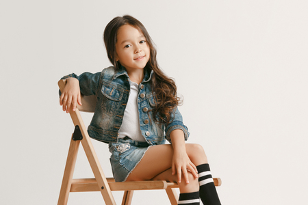 The portrait of cute little kid girl in stylish jeans clothes looking at camera and smiling, sitting against white studio wall. Kids fashion concept Stock Photo