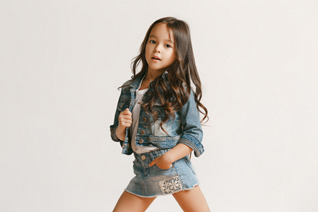 Full length portrait of cute little kid girl in stylish jeans clothes looking at camera and smiling, standing against white studio wall. Kids fashion concept Stock Photo