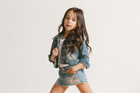 Ganzaufnahme eines süßen kleinen Mädchens in stilvoller Jeanskleidung, das die Kamera anschaut und lächelt und gegen die weiße Studiowand steht. Konzept für Kindermode