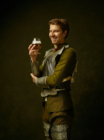 Medieval smiling happy knight with beer on dark studio background. Portrait in low key of brutal man in tradishional retro costume of spanish hidalgo. Human emotions, comparison of eras concept 스톡 콘텐츠