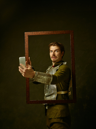 Medieval knight with mobile phone on dark studio background. Portrait in low key of brutal man in tradishional retro costume of spanish hidalgo. Human emotions, comparison of eras concept