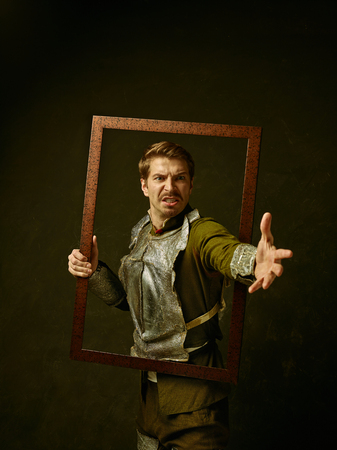 Medieval angry knight on dark studio background. Portrait in low key of brutal man in tradishional retro costume of spanish hidalgo. Human emotions, comparison of eras and facial expressions concept