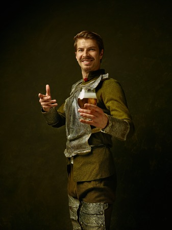 Medieval smiling happy knight with beer on dark studio background. Portrait in low key of brutal man in tradishional retro costume of spanish hidalgo. Human emotions, comparison of eras concept Stock Photo