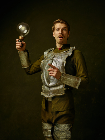 Medieval suirprised knight with lamp on dark studio background. Portrait in low key of brutal man in tradishional retro costume of spanish hidalgo. Human emotions, comparison of eras concept Stock Photo