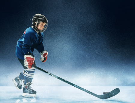 Little boy playing ice hockey at arena. A hockey player in uniform with equipment over a blue background. The athlete, child, sport, action concept 写真素材