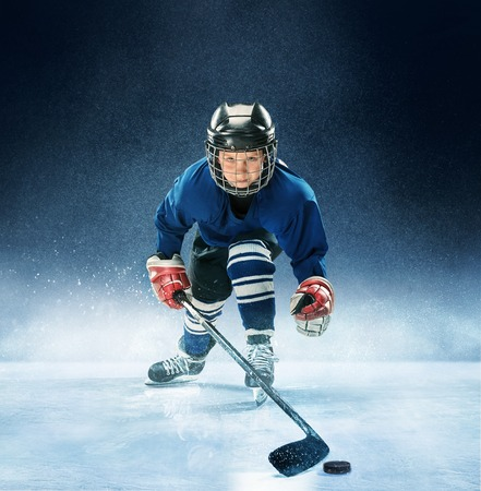 Little boy playing ice hockey at arena. A hockey player in uniform with equipment over a blue background. The athlete, child, sport, action concept 스톡 콘텐츠