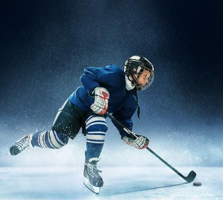 Kleiner Junge, der Eishockey in der Arena spielt. Ein Hockeyspieler in Uniform mit Ausrüstung auf blauem Grund. Das Athlet, Kind, Sport, Aktionskonzept