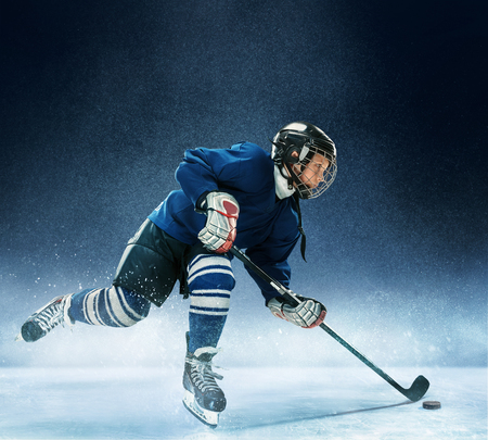 Little boy playing ice hockey at arena. A hockey player in uniform with equipment over a blue background. The athlete, child, sport, action concept Zdjęcie Seryjne