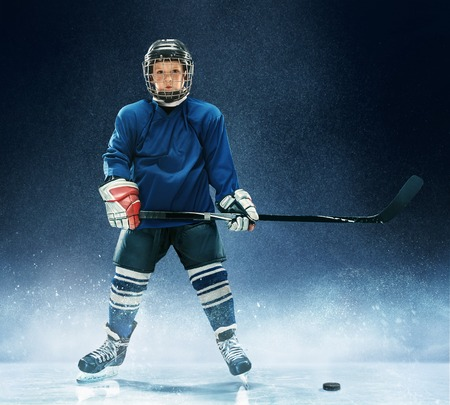 Little boy playing ice hockey at arena. A hockey player in uniform with equipment over a blue background. The athlete, child, sport, action concept Banco de Imagens
