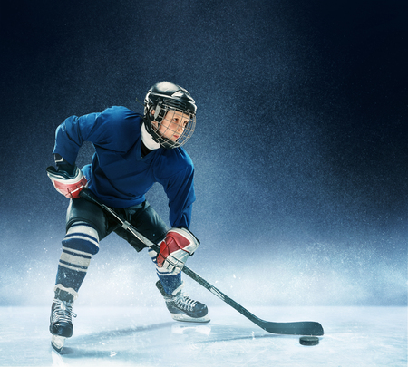 Little boy playing ice hockey at arena. A hockey player in uniform with equipment over a blue background. The athlete, child, sport, action concept Stock Photo