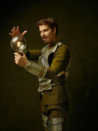 Medieval knight with lamp on dark studio background. Portrait in low key of brutal man in tradishional retro costume of spanish hidalgo. Human emotions, comparison of eras and facial expressions concept Stock Photo