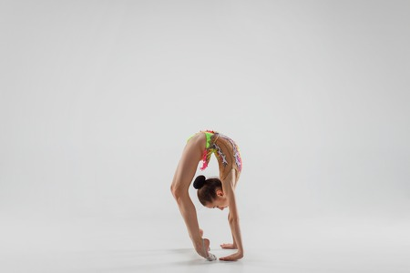 The teen female little girl doing gymnastics exercises isolated on a gray studio background. The gymnastic, stretch, fitness, lifestyle, training, sport concept