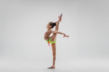 La bambina femmina adolescente facendo esercizi di ginnastica isolata su uno sfondo grigio studio. La ginnastica, l'allungamento, il fitness, lo stile di vita, l'allenamento, il concetto di sport