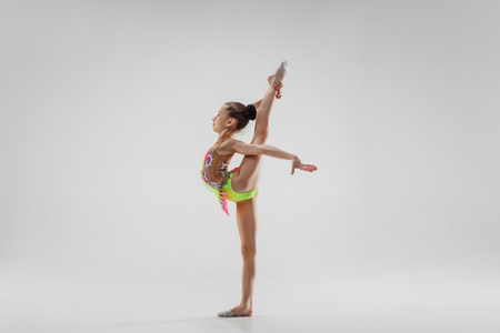 The teen female little girl doing gymnastics exercises isolated on a gray studio background. The gymnastic, stretch, fitness, lifestyle, training, sport concept 免版税图像 - 112888790