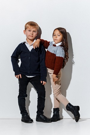 The portrait of cute little kids boy and girl in stylish jeans clothes looking at camera against white studio wall. Kids fashion and happy emotions concept
