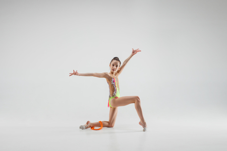 The teen female little girl doing gymnastics exercises with jump rope isolated on a gray studio background. The gymnastic, stretch, fitness, lifestyle, training, sport concept
